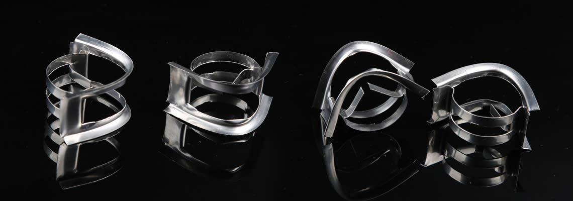 Several stainless steel nutter rings lying on the black glass in different posture.